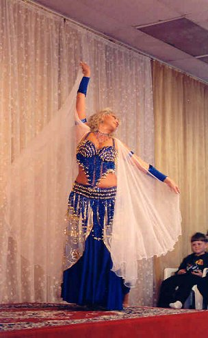 dancer in dark blue with sheer white cape veil
