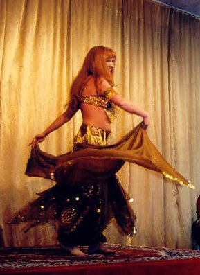 dancer in gold and black spins with veil