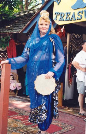 dancer in blue poses with tambourine