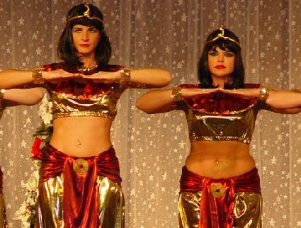 dancers in red and gold liquid lame and snake headdresses