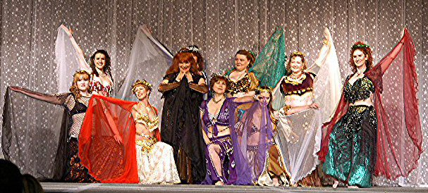 dancers pose on stage with cape veils outstretched