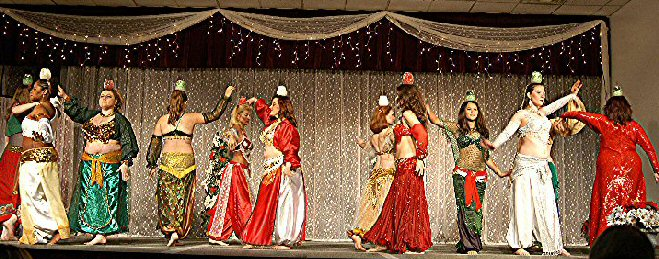 dancers in christmas colors balancing candles on heads