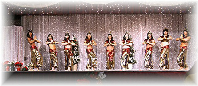 group of dancers in red and gold liquid lame and snake headdresses and short black wigs