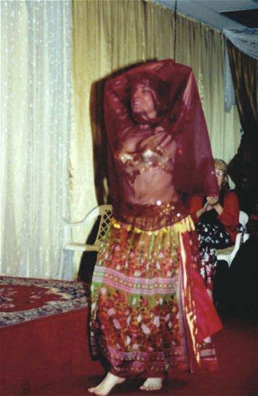 dancer smiles under sheer wine colored veil