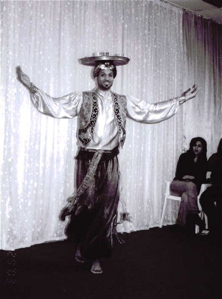 grayscale of photo of male performer balancing a candle tray on head while dancing