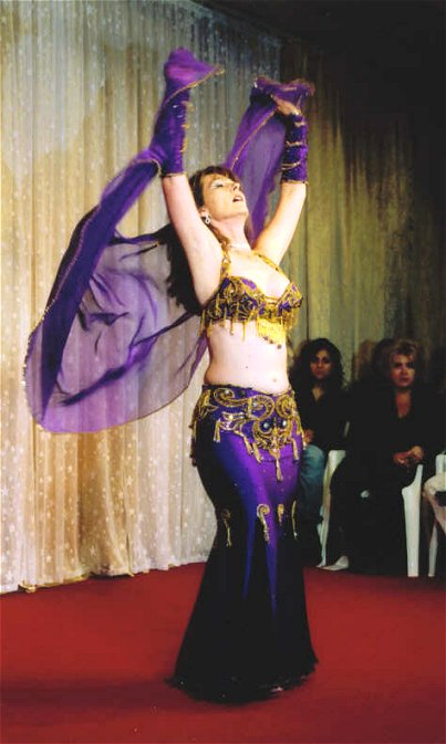 dancer wearing purple and gold on stage with veil flowing