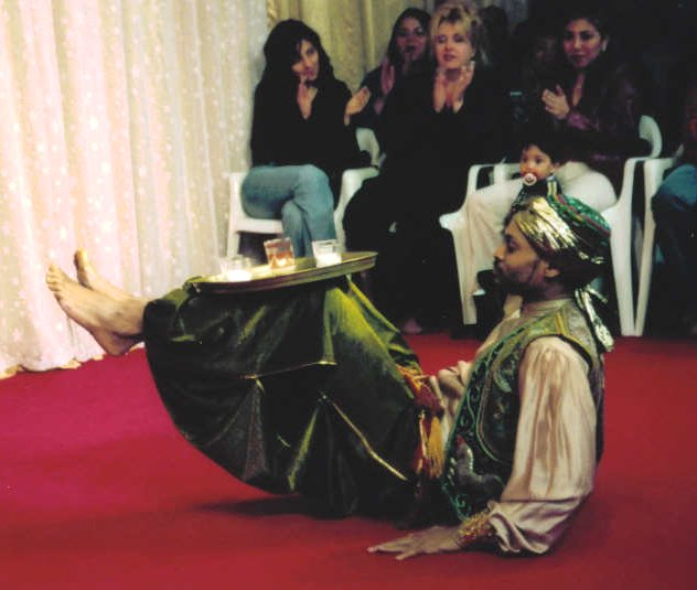 male dancer balances a tray of candles on his legs