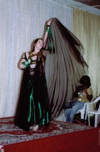dancer in shiny dark green with sheer cape veil