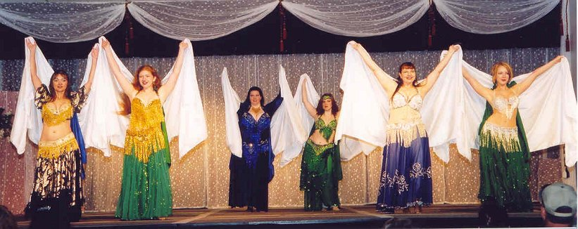 group of dancers in blues and greens with white veils